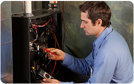 A Reliance Holmes technician repairs a furnace