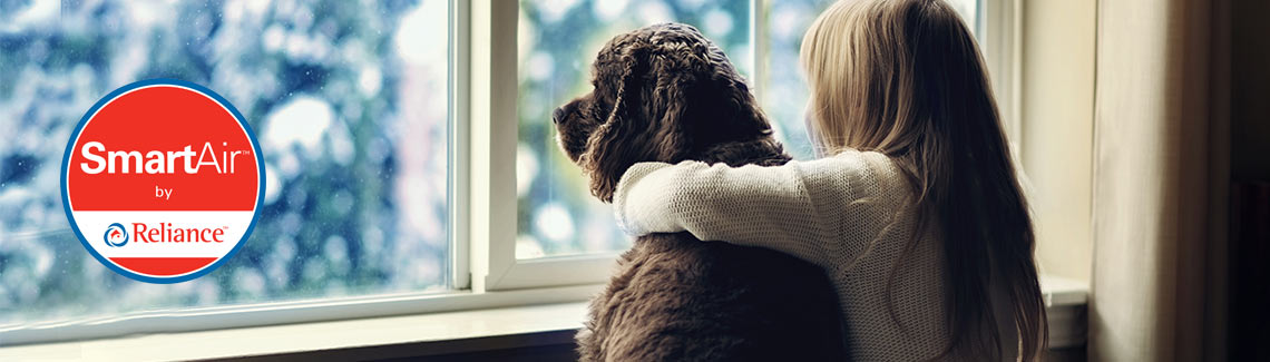 A girl and her dog are warm thanks to a high efficiency furnace by Reliance Home Comfort